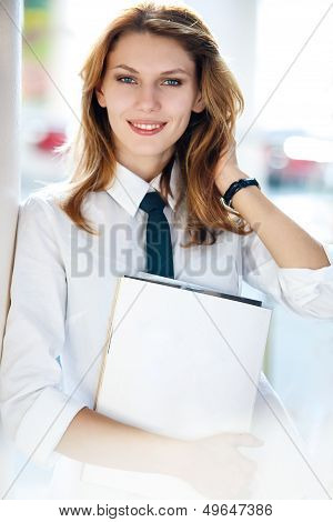 Delightful young woman holds the folder