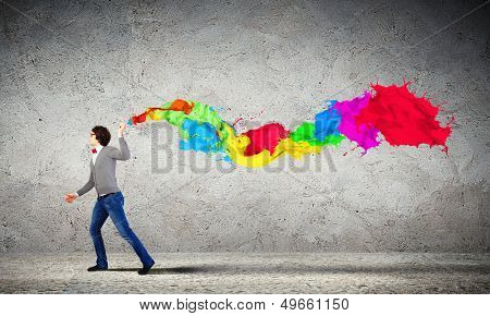 Young man spraying colour paints over background poster