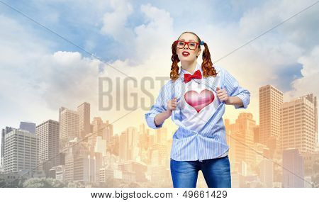 Young woman acting like super hero with heart sign on chest