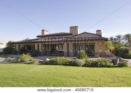Sunlit garden exterior of home against clear sky poster