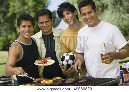 Portrait of happy male friends barbecuing food at park