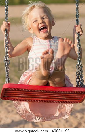 Cute Little Girl Laughs While Swinging