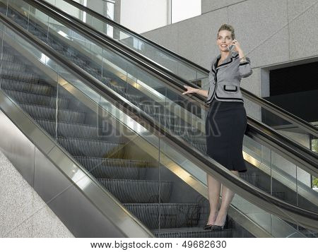Full length of businesswoman using mobile phone on escalator