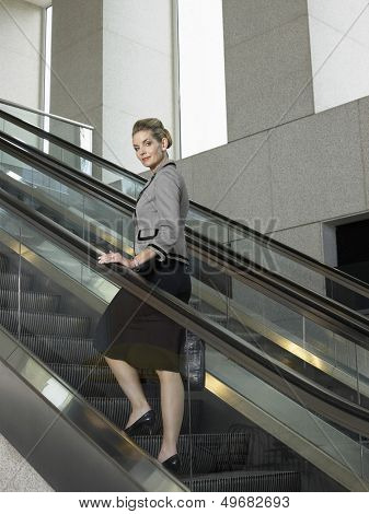 Full length portrait of confident businesswoman standing on escalator