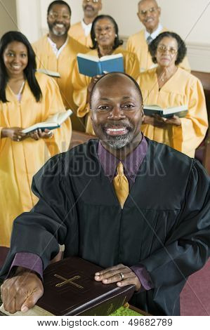 Portrait of happy preacher with Holy Bible while choir standing in background at church