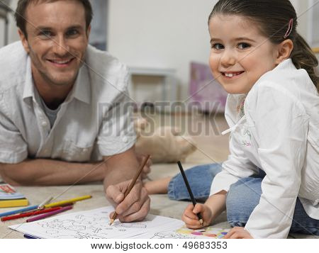 Portrait of little girl with father coloring book on floor at home