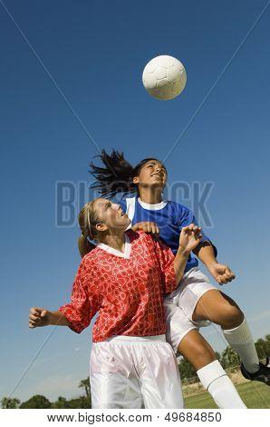 Girls heading soccer ball during match against blue sky