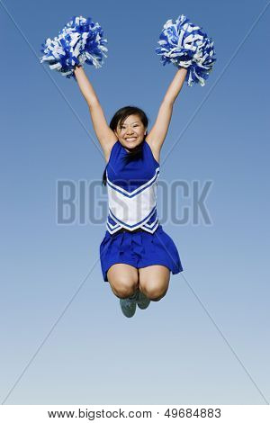 Full length of excited cheerleader with pompoms in midair against blue sky