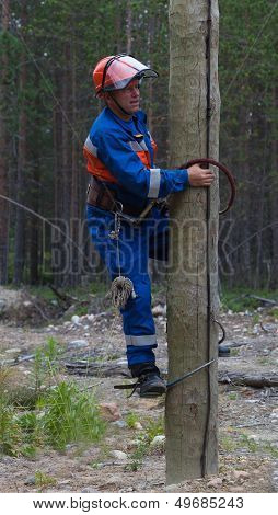 Electrician Begins To Climb On A Power Pole