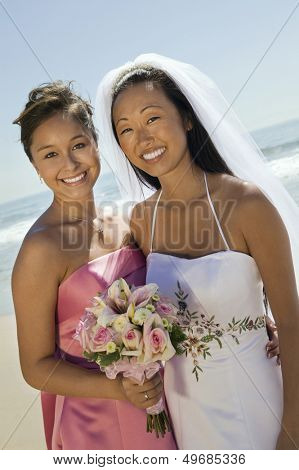 Portrait of beautiful young bride and bridesmaid with flower bouquet smiling on beach
