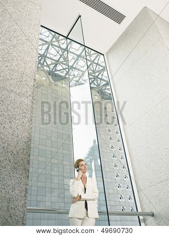 Low angle view of businesswoman using mobile phone in office building