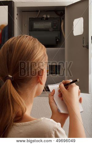 Young woman rewrites the electrical meter readings
