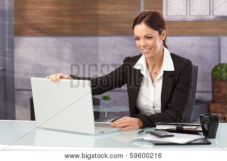 Happy businesswoman sitting at desk shutting down laptop computer, finishing work.