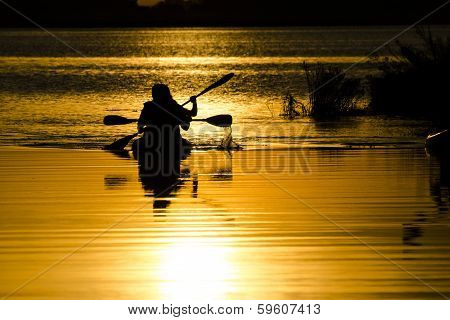 Silhouettes of men kayaking in the lake at sunset