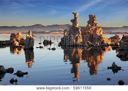 Outliers -  bizarre calcareous tufa formation  reflected in the mirrored surface of the water. The picturesque sunset at Mono Lake. Yosemite National Park, USA