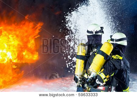 Firefighter - Firemen extinguishing a large blaze, they are standing with protective wear in front of wall of fire