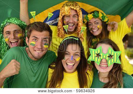 Happy group of Brazilian sport soccer fans amazed celebrating victory together.