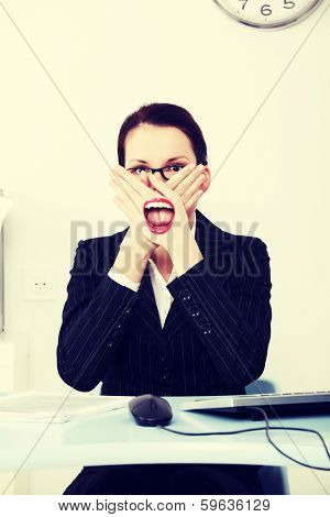 Businesswoman covering her mouth with hands not to say anything immoral during work.