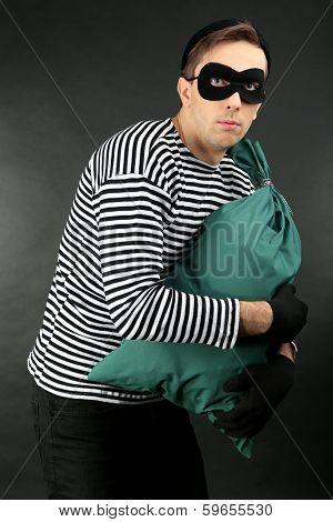 Thief with bag on dark background