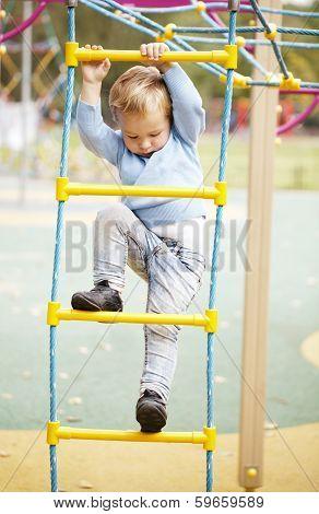 Cute little boy climbing on a jungle gym