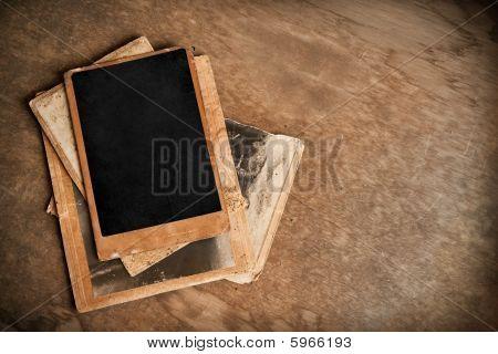 Vintage photo frames on aged wooden background