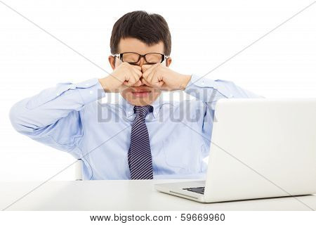 Tired Young Businessman Rubbing His Eyes With Laptop