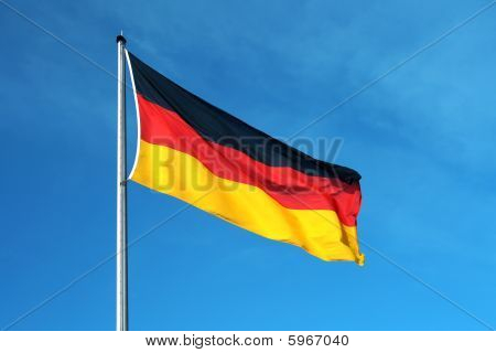 The national German flag with a blue sky in the background. poster