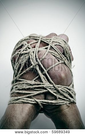 man hands tied with string, as a symbol of oppression or repression, on a white background