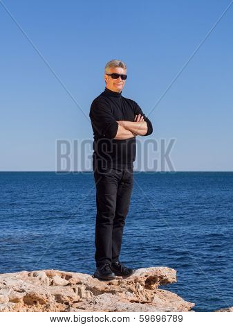 Mature Businessman Posing Confident On A Rock At The Sea
