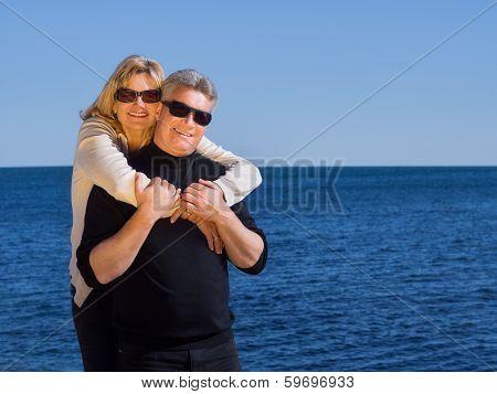 Happy Loving Mature Couple Posing Against A Blue Ocean