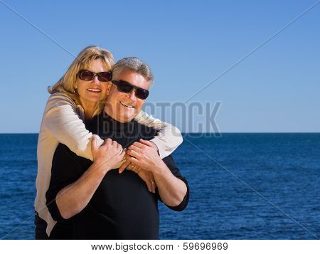 Smiling Healthy Tanned Mature Couple On Beach