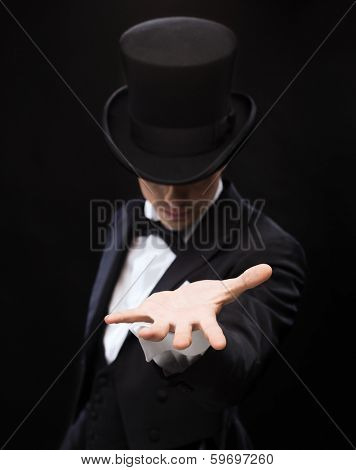 magic, performance, circus, show and advertisement concept - magician holding something on palm of his hand