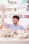 angry student surrounded by books throws a book in his room poster
