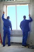 Two men in working clothes set new window frame into the window opening poster