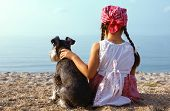 beautiful little girls embracing her dog looking at the sea poster