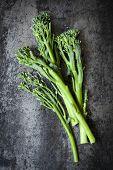 Broccolini on dark slate.  Overhead view. poster