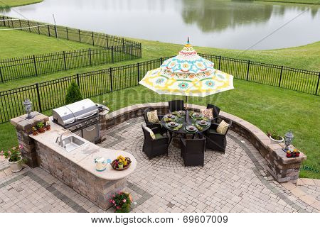 Outdoor living space on a brick patio overlooking a tranquil lake and fenced green lawn with a table under a sunshade or umbrella laid ready for dinner high angle view poster