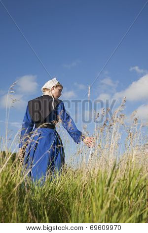 Low Angle View Of Amish Girl Walking In A Field