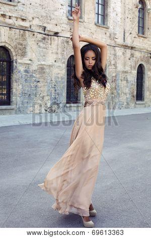 beautiful girl with dark hair in luxurious dress