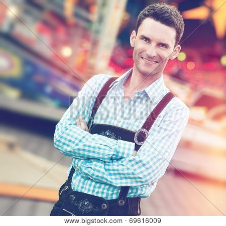 Handsome guy wearing Bavarian Lederhosen trousers with his arms folded