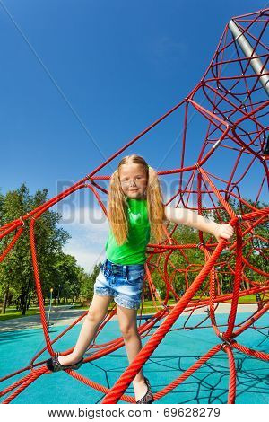 Cute girl balancing on red rope of web outside