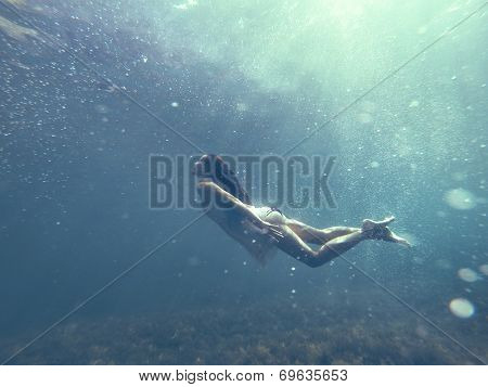 Underwater photo of a human diving in blue sea water