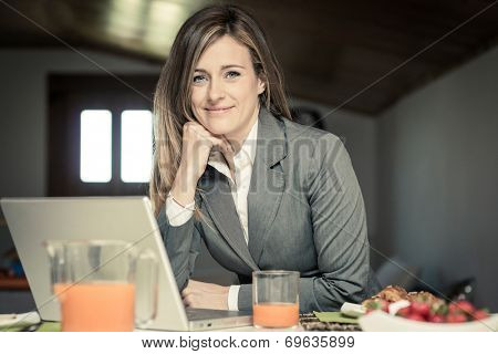 Smiling businesswoman working at home during breakfast