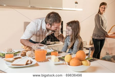 Father having breakfast with his little girl, mother in the background on playpen