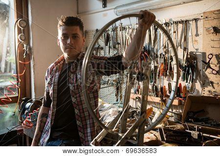 Young man working in a biking repair shop