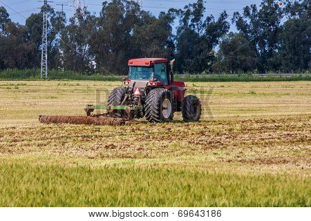 SDE YOAV, ISRAEL - MARCH 21, 2009: Tractor plowing the agricultural field of Sde Yoav kibbutz. First kibbutz was established in 1909 and it is collective community traditionally based on agriculture.