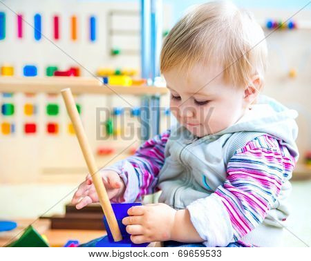 cute little girl in the classroom early development plays with numerous bright toys