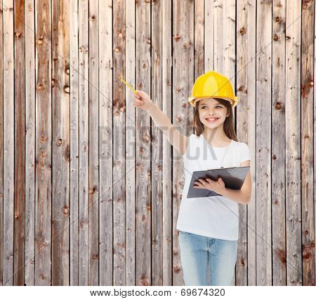 childhood, construction, architecture, building and people concept - smiling little girl in protective helmet with clipboard pointing pencil