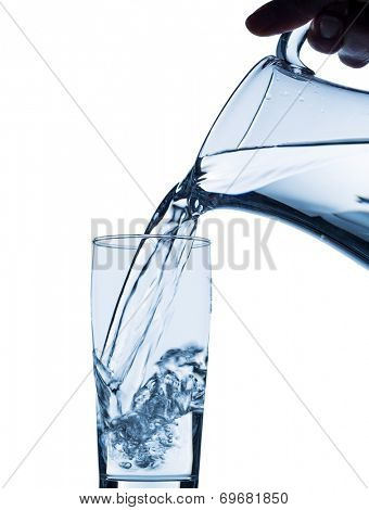 pure water is emptied into a glass of water from a pitcher. fresh drinking water
