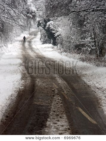 A man walking along a winter snow covered road